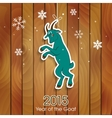 Green goat decoration on a wooden background vector image