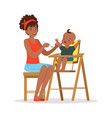 happy young african mother feeding her baby in vector image