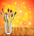 Art brushes in glass on wooden table colorful vector image