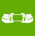 two hands holding mobile phone icon green vector image