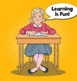 Pop art happy schoolgirl sitting at school desk vector image
