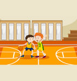 two boys playing basketball in the gym vector image