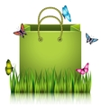 Green paper shopping bag on the meadow grass vector image