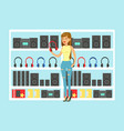 young woman choosing headphones at tech store vector image