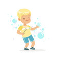 cute little blonde boy playing bubbles vector image