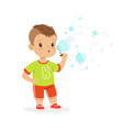 cute little boy playing with bubble blower vector image