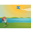 A young boy playing with his kite at the riverbank vector image vector image