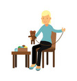 young woman sitting on the chair and sewing vector image