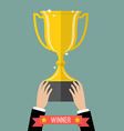 Hand holding up a winning trophy vector image