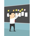 Businessman pinning sheets of paper on blackboard vector image