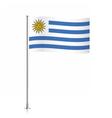 Uruguay flag waving on a metallic pole vector image