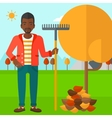 Man with rake near tree and heap of leaves vector image