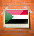 Flags Sudan scotch taped to a red brick wall vector image