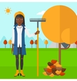 Woman with rake near tree and heap of leaves vector image