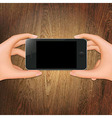 Wooden Background With Hands Holding Phone vector image vector image