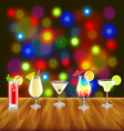 Cocktails on wooden table and bar lights vector image