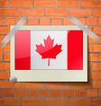 Flags Canada scotch taped to a red brick wall vector image