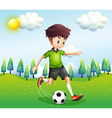 A boy playing football in the hill vector image