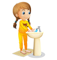 A cute young girl washing her hands vector image vector image
