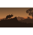 Triceratops and Eoraptor silhouette in hills vector image
