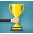 Hand holding a winner trophy cup vector image vector image