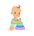 cute smiling baby sitting and playing with pyramid vector image