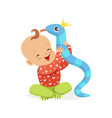 sweet smiling baby playing with toy snake vector image