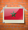 Flags Morocco scotch taped to a red brick wall vector image
