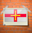 Flags Guernsey scotch taped to a red brick wall vector image