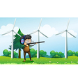 A boy shooting in front of the windmills vector image