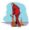 Road worker puts traffic cones vector image