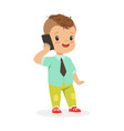 cute little boy standing and talking on mobile vector image vector image