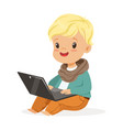 cute little boy sitting and using laptop for vector image