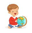 smiling little boy sitting and playing with globe vector image