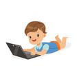 happy little boy lying on the floor using laptop vector image