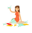 cheerful young woman making origami cranes from vector image