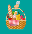 hand holds wicker picnic basket full of products vector image