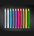 color pencils lying on black chalkboard vector image