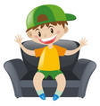 boy sitting on gray armchair vector image