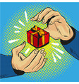 gift box in hand with golden bow and ribbons pop vector image