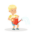 cute happy little boy standing with a red watering vector image