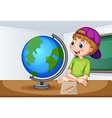 Boy looking at globe in classroom vector image