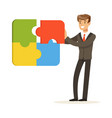 smiling businessman assembling colorful jigsaw vector image