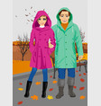 young couple wearing raincoats in park in autumn vector image