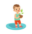 cute little boy standing and holding a plant in a vector image