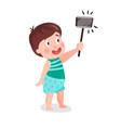 Cute cartoon little boy making selfie with a stick vector image
