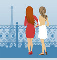 two women look at the eiffel tower in paris vector image