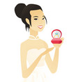 young asian bride holding a wedding ring in a box vector image