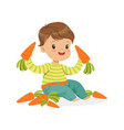 cute little boy sitting and playing with carrots vector image