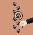 hand holding magnifying glass over paw print vector image